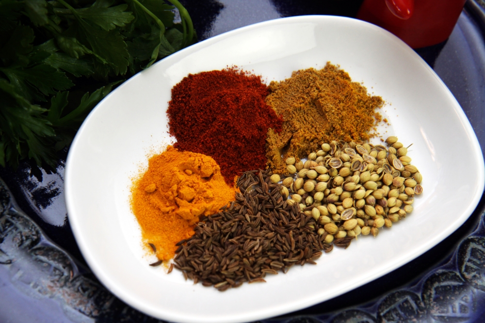 Clockwise from left: turmeric, chilli powder, garam masala, coriander seeds and caraway seeds. Photo: Nicholas Rider.